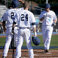 UNCW's Corey Dick crosses homeplate as Ryan LaGrange, left, and Luke Dunlap wait to congratulate him after a two run homer in the first. (Jason A. Frizzelle)