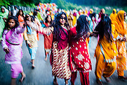 A group of girls take part in a procession to the river. As part of their Puja ceremony, these Rajasthani nomadic peoples spend ten days worshiping the goddess Dashama. At the end of the Puja, the followers march to the river where the goddess' likeness is given back to the river and elements.