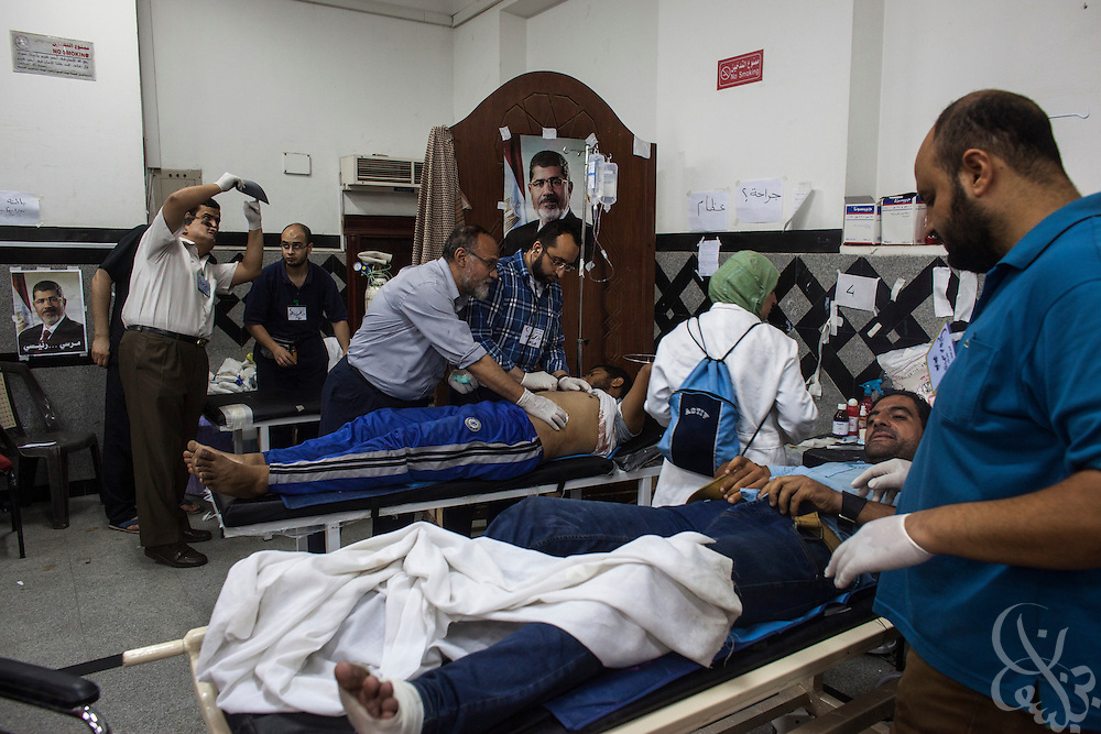 Muslim Brotherhood doctors treat those wounded in an attack on a march by supporters of deposed Egyptian president Mohamed Morsi early Wednesday July 24, 2013 at a makeshift emergency hospital inside the Rabia al-Adawiyya Square protest camp in the Nasr City district of Cairo, Egypt. Two in the marchers were killed, and a dozen wounded when unknown gunmen fired on them in a nearby area.