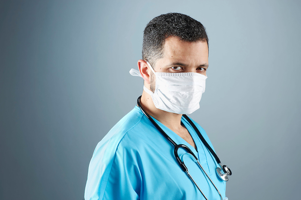 A portrait series representing the intense emotions that Doctors face.  A Puerto Rican male Doctor wearing a white surgical mask, stethoscope, and blue medical scrub suit shown.
