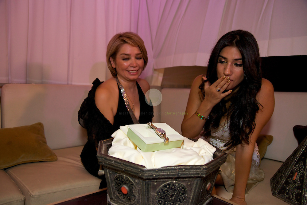 Laila Banki and her aunt sitting at the outdoor terrace of Dubai's elite Sanctuary Club, located at the iconic Atlantis Hotel on The Palm Jumeirah. Laila's aunt presents her the ultimate birthday present: a new Rolex watch. Laila looks at the watch in disbelief.