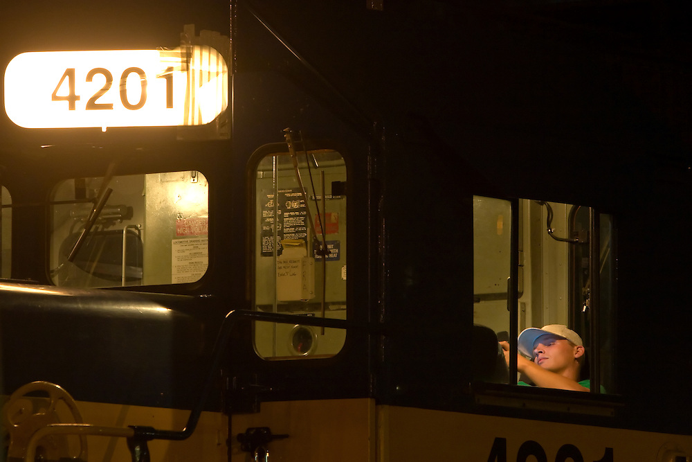 An Iowa Chicago & Eastern railroad conductor relaxes as his westbound train waits in the siding in Genoa, IL for an eastbound to show up.