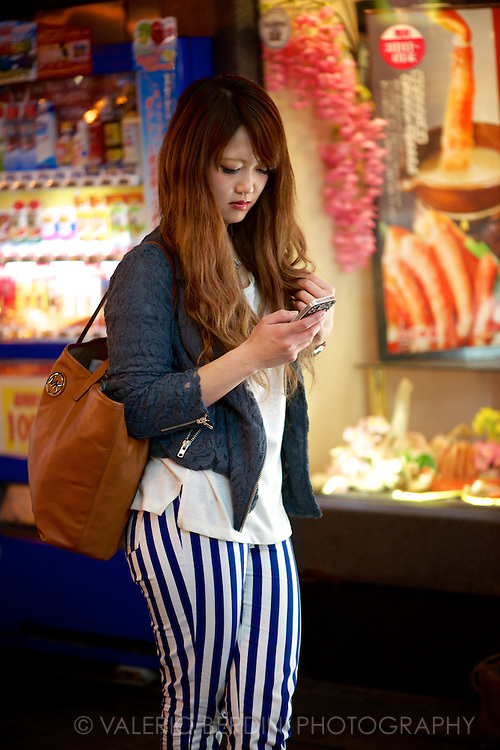 A girl texts in front of a colourful shop window. Osaka, Japan 2013