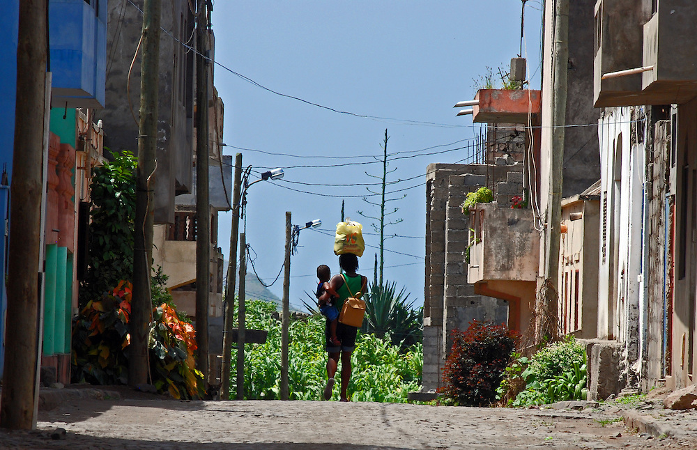 A Cape Verdean girl walks along a cobbled street carrying a young child on her hip and a shopping bag on her head.  Assomada, Santiago, Cape Verde (Cabo Verde). Assomada lies on a plateau in central Santiago.