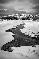 A frozen part of the Provo River leads to Mount Timpanogos on a cold Winter morning in Utah's Wasatch Mountains.