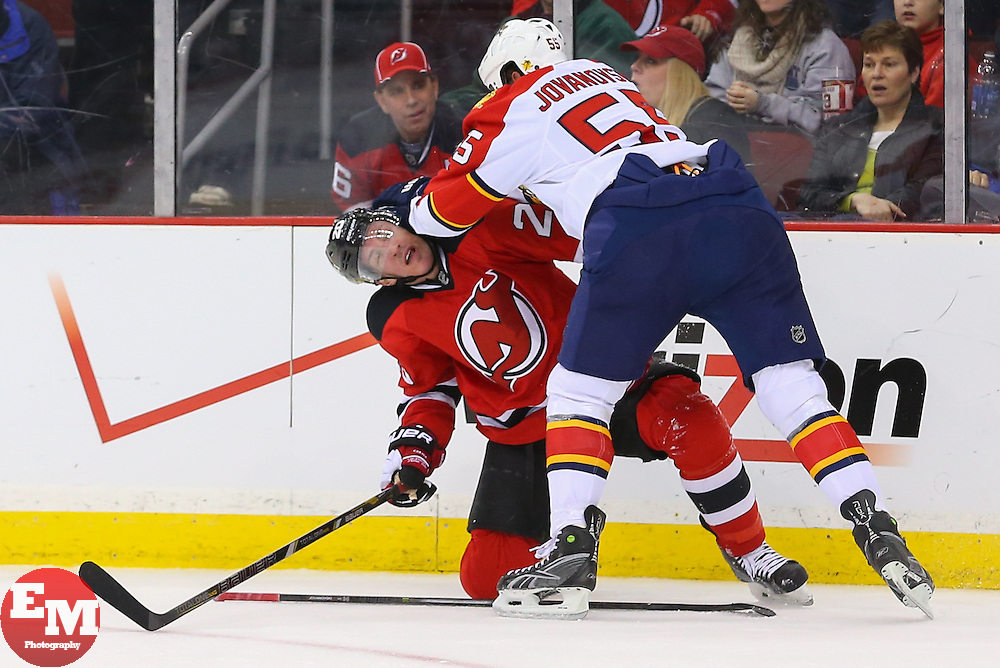 Mar 31, 2014; Newark, NJ, USA; Florida Panthers defenseman Ed Jovanovski (55) hits New Jersey Devils center Ryan Carter (20) in the head during the first period at Prudential Center.