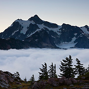 "Thick fog covers a high mountain valley beneath Mount Shuksan, a 9,127-foot (2,782-meter) peak located in the North Cascades National Park in Washington state. Valley fog, which is a type of radiation fog, can be incredible dense. It forms when air along ridgetops and mountain slopes cools after sunset. The air then becomes dense and sinks into the valley below where it continues to cool and becomes saturated, causing fog to form. Shuksan is derived from a Skagit Indian word meaning ""rocky and precipitous."""