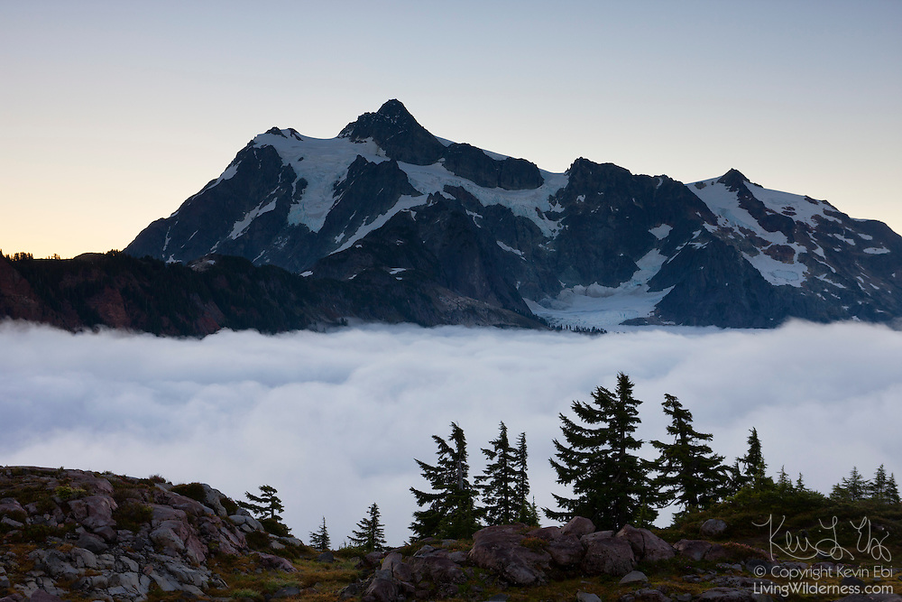 """Thick fog covers a high mountain valley beneath Mount Shuksan, a 9,127-foot (2,782-meter) peak located in the North Cascades National Park in Washington state. Valley fog, which is a type of radiation fog, can be incredible dense. It forms when air along ridgetops and mountain slopes cools after sunset. The air then becomes dense and sinks into the valley below where it continues to cool and becomes saturated, causing fog to form. Shuksan is derived from a Skagit Indian word meaning """"rocky and precipitous."""""""
