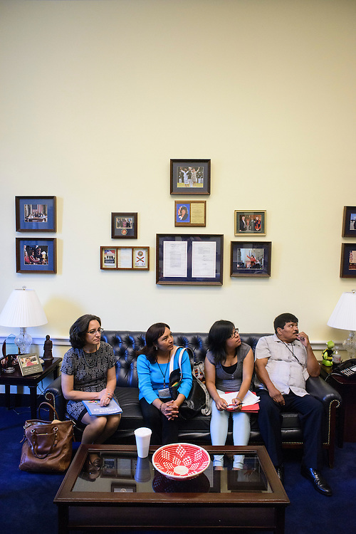 Photo by Matt Roth<br /> <br /> Virginia Ruiz, with Farmworker Justice, and Florida Farmworker Fly In constituents (L-R) Ofelia Aguilar, Selena Zelaya and her father  Miguel Zelaya, wait to meet with Lee Footer, Legislative Assistant for Agriculture &amp; Environmental Policy for Rep. Corrine Brown at the Rayburn House Building in Washington, D.C. on Tuesday, July 16, 2013.