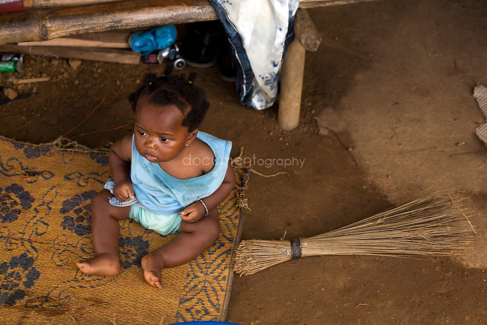 A child on the porch of a house, Kingsville #7, Liberia.