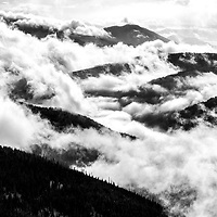 Clouds form in the deep valleys while the Kootenay mountain range peeks through
