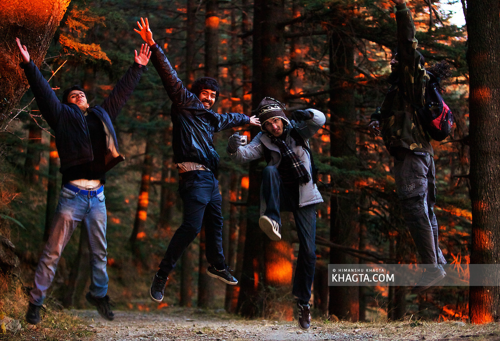 Friends posing for a shot at sunset time when the orange rays of the sun were falling on the green pine trees in a forest in Shimla