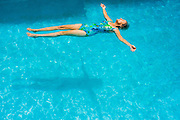 Senior woman floating on her back in a swimming pool