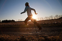 Woman running on a country road at sunset.