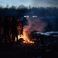 A group of migrants warm at a wooden fire  at sunset. Wood is the only way to warm in the camp where there is no electricity. Grande Synthe, France. FEDERICO SCOPPA/CAPTA