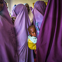 Young girl clinging to her mother during a meeting of the Mada Saving Club in Tsafe, Nigeria.  The Club is for women and has over 5500 members. Every week, women give money and when they need it, they can borrow with a small interest not payable until after the first month.