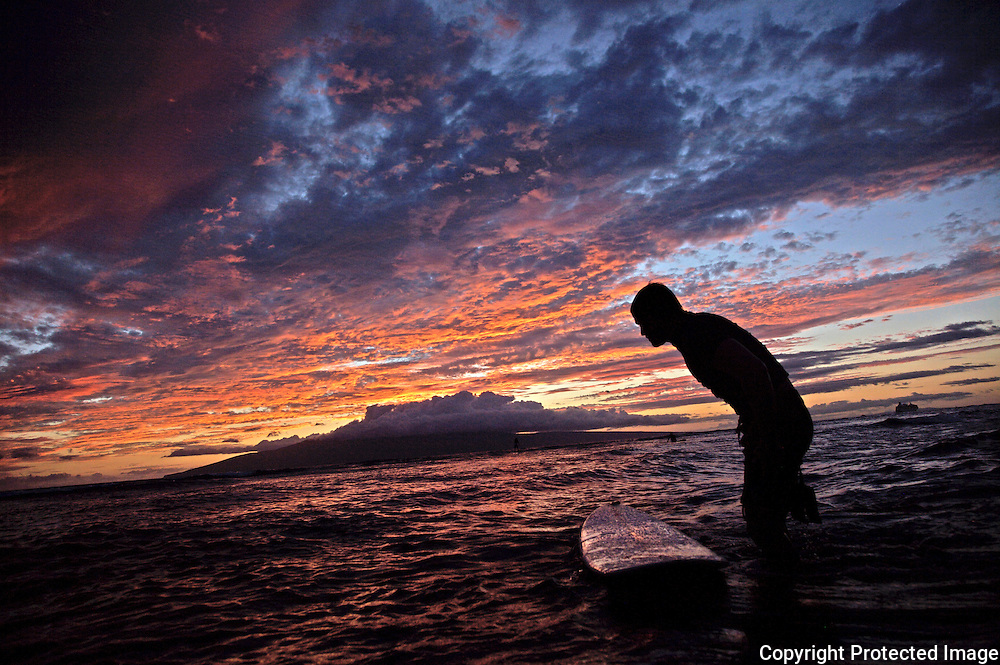 A surfer is ready to test the final waves on Maui, as a beautiful sunset frames the horizon.