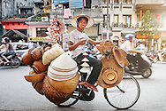 A street vendor on wheels sells many hats from his mobile storefront in Hanoi, Vietnam.