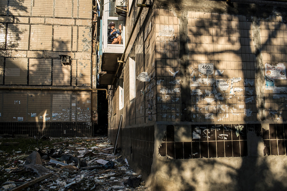 A woman tapes the window of her apartment after the building was hit by a suspected grad rocket strike on Tuesday, July 29, 2014 in Donetsk, Ukraine.
