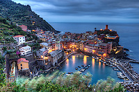 """Vernazza has no car traffic, and remains one of the truest """"fishing villages"""", probably the most characteristic of the Cinque Terre and is classified as one of the most beautiful villages in Italy. It was founded about 1000 A.D. and was ruled by the Republic of Genoa starting in 1276. The tiny port is surrounded by subtle colourful pastels and the charming piazza is lined with good restaurants and bars. The village is surrounded by very steeply-terraced olive groves which are said to produce among the finest olive oil in the country."""