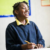 A student smiling during her after school work at the Epiphany School in Dorchester photographed for the school's Annual Report.