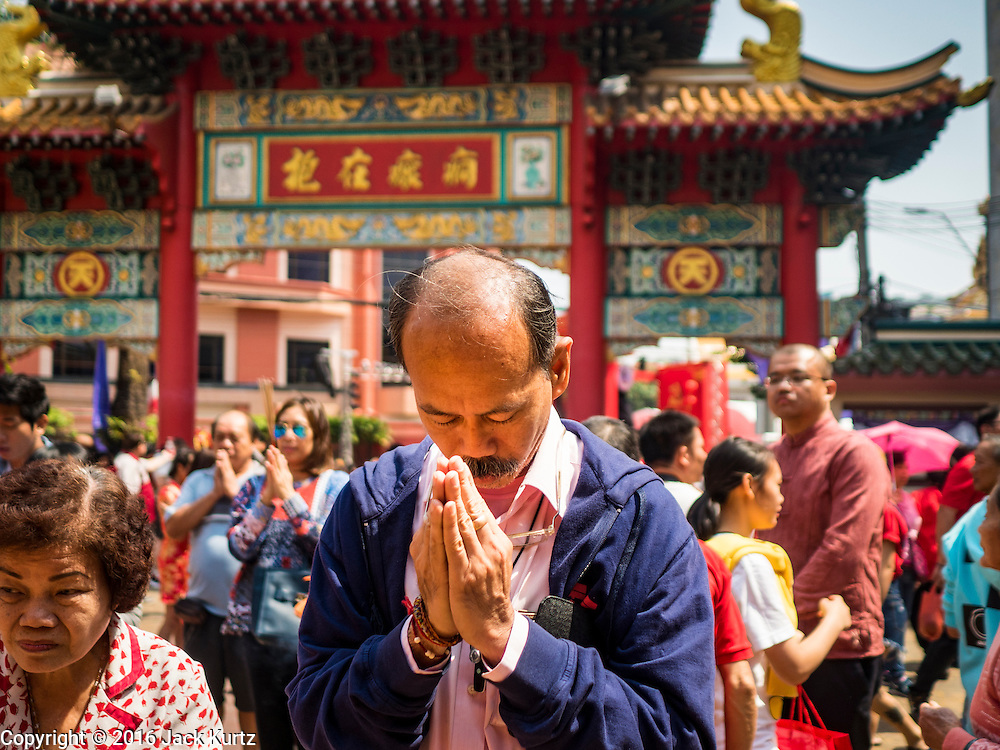 """08 FEBRUARY 2016 - BANGKOK, THAILAND: A man prays during Chinese New Year observances at Kuan Yim Shrine in Bangkok's Chinatown district, during the celebration of the Lunar New Year. Chinese New Year is also called Lunar New Year or Tet (in Vietnamese communities). This year is the """"Year of the Monkey."""" Thailand has the largest overseas Chinese population in the world; about 14 percent of Thais are of Chinese ancestry and some Chinese holidays, especially Chinese New Year, are widely celebrated in Thailand.       PHOTO BY JACK KURTZ"""