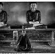 A buddhist monk sits at a temple in Sitteway, Myanmar, Friday, Dec. 20, 2013.