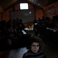SYRIA, ATMEH. The makeshift school inside the camp for displaced Syrians in Atmeh on January 12, 2013. As there is no electricity, classes are given in the dark. The camp is on the border with Turkey and is providing shelter to nearly 13,000 people; most of them are children. ALESSIO ROMENZI