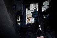 A blanket replacing a window is seen in the rubble of Shejaiya