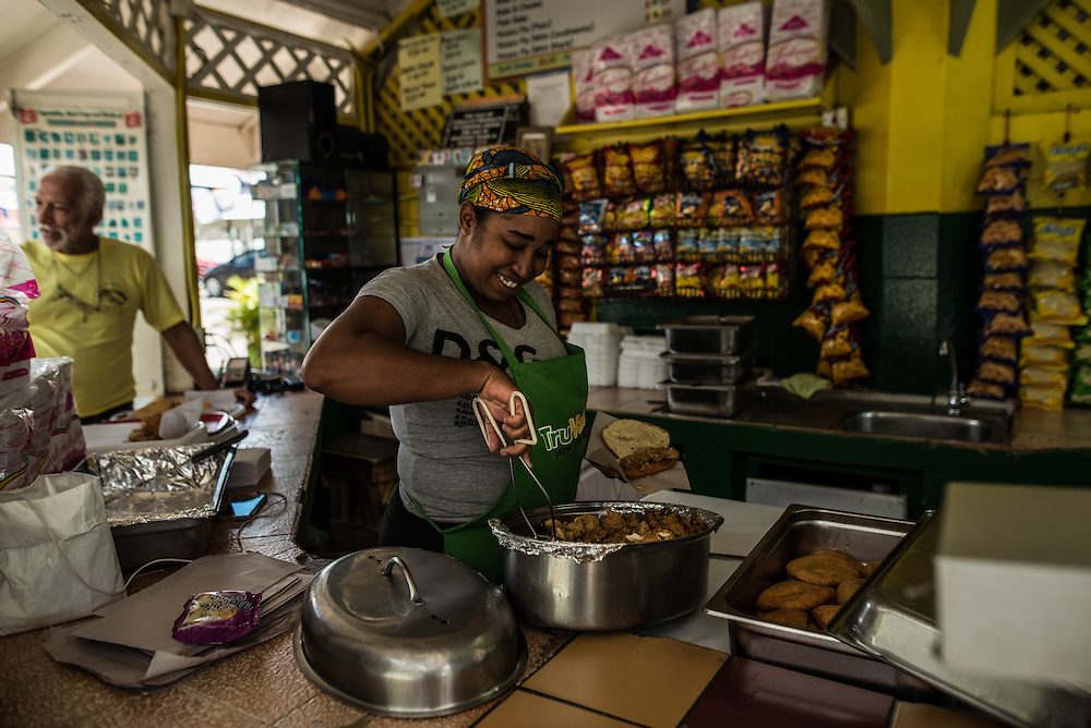 """MARACAS BAY, TRINIDAD - FEBRUARY 14, 2017:   Half the reason locals come to Maracas Bay is for the """"shark n' bake"""" that's sold at a number of seaside food stands: a portion of hammerhead shark  battered and fried, then tucked into the """"bake"""", a folded-over circle of freshly fried bread (30TT). Add a cold Carib beer to help you cool off. PHOTO: Meridith Kohut for The New York Times"""