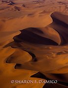 """In the Nama language, Namib means """"vast.""""  On an early morning flight over these, the highest dunes in the world, I was astounded at their beauty.  I love how slanted light alters the landscape with bands of orange-red and deep shade. A Limited Edition Print."""
