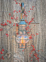 A barn lantern fixture with red berries.