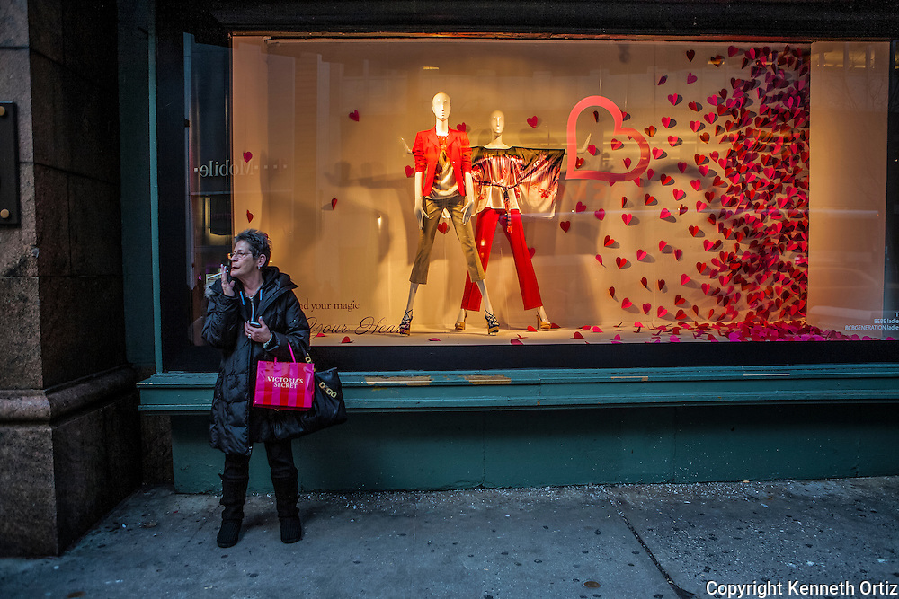 A woman smoking her cigarette in front of Macy's window on 34th Street.
