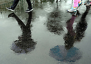 Spectators walk to the first tee in the rain during the second round of the RBC Heritage golf tournament in Hilton Head Island, S.C., Friday, April 18, 2014. (AP Photo/Stephen B. Morton)