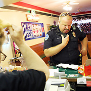 Grants Pass Police Officer Kevin Blaich calls dispatch while searching for heroin that allegedly fell out of a lottery ticket thief's folded piece of foil at the Purple Parrot, a lottery center. Since federal timber payments have ceased in Josephine County and other parts of Southwest Oregon, the tax-base has shrunk. In Grants Pass, the county seat, shoplifting and other property crime are up, and law enforcement personnel numbers are down. The shoplifters were cited and released.