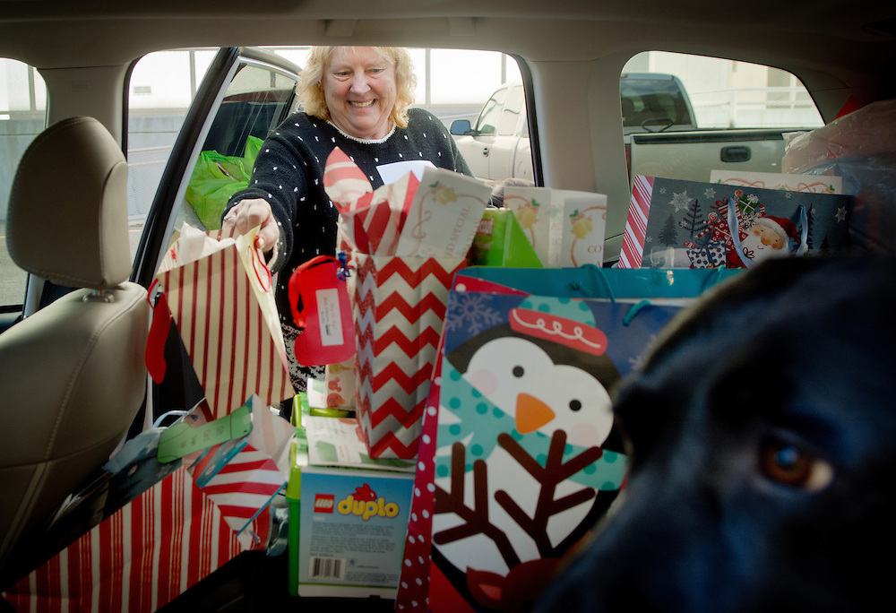 mkb122016/metro/Marla Brose122016<br /> Sandra Gatzke, from New Mexico Kids Matter, fills up the backseat of a car, next to Cassie, a New Mexico Kids Matter courthouse dog, with gifts for foster children in state custody from the Second Judicial District Court, Tuesday, Dec. 20, 2016, in Albuquerque, N.M. Private donors from the court gave about $5000 worth of gifts, including toys, winter and professional clothing and animal supplies, for foster children, transitioning veterans at the New Mexico Veterans Integration Center and for animals from Animal Humane New Mexico in this year's Giving Tree project. (Marla Brose/Albuquerque Journal)