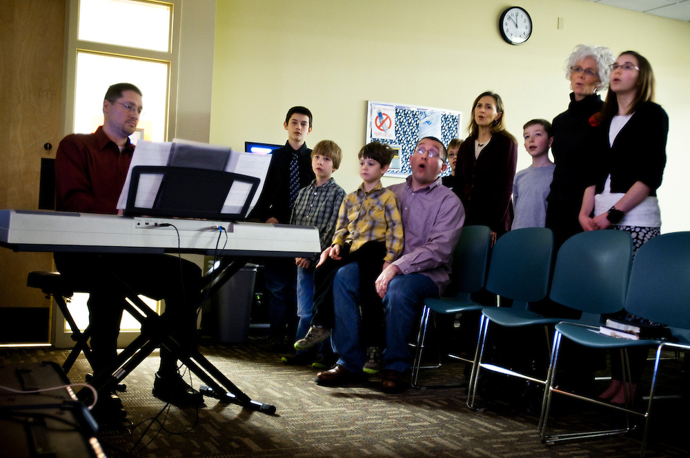 John Hanson playing the piano at his church (Oikos Community Church) while his children and other members of the congregation sing during the Sunday service...John is currently unemployed after recently coming back from military duty in Iraq - he is part of the National Guard.