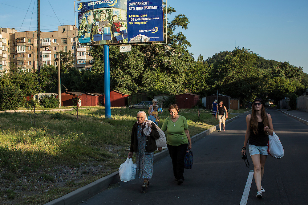 Local residents carry their belongings to a shelter on Tuesday, July 29, 2014 in Donetsk, Ukraine.