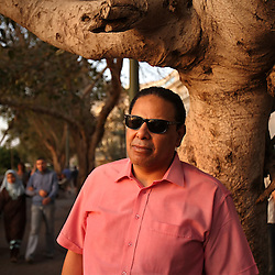 Ala'a Al-Aswany, a prominent Egyptian writer and founding member of the political movement Kefaya, walks near the Nile River in Cairo, Egypt on April 4, 2008. Trained as a dentist in Cairo and Chicago, Al-Aswany has contributed numerous articles to Egyptian newspapers on literature, politics, and social issues. His second novel, The Yacoubian Building, an ironic depiction of modern Egyptian society, has been widely read in Egypt and throughout the Middle East. It was translated into English and was adapted into a film (2006) and a television series (2007) of the same name. Chicago, Al-Aswany's latest novel, is set in the American city where he had attended college.