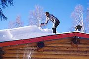 Alaska. A man shoveling snow off roof of Fairbanks home. (MR)