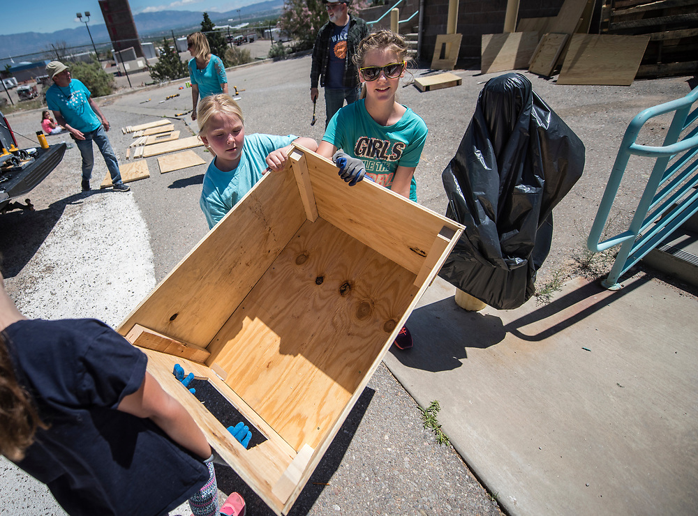 rer042217k/Fetch/04.22.2017/Roberto E. Rosales <br /> Girls Scouts came together at the Westside shelter on Saturday April 22nd to build and paint dog houses for people who can't afford them in hopes of encouraging people not to give up their dogs because they can't provide a house for them.  Pictured are Nora Sharp(Cq),10, left,  Minka Smith (Cq),10,center, and Elle Bousliman(Cq),10,right, carrying a house to be painted. <br /> Albuquerque, New Mexico(Roberto E. Rosales/Albuquerque Journal)