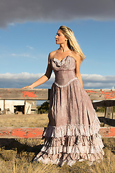 beautiful girl in a Western dress outdoors on a ranch