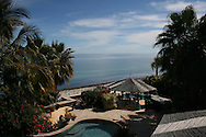 Ocean view from the roof of a beach front home, featuring a pool and luch gardens with palm trees.