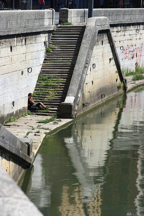 A young woman hangs out on the steps along the riverbank of the Saône in Lyon, France