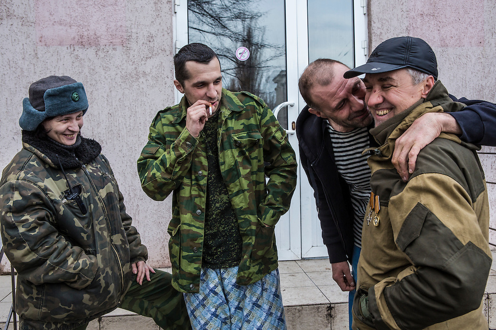 GORLOVKA, UKRAINE - JANUARY 31, 2015: Batya, a rebel commander right, is greeted by a wounded comrade outside a hospital as Ira, left, and another wounded fighter look on in Gorlovka, Ukraine. Fighting in Ukraine has intensified over the last week, with rebels declaring the end of a September ceasefire. CREDIT: Brendan Hoffman for The New York Times