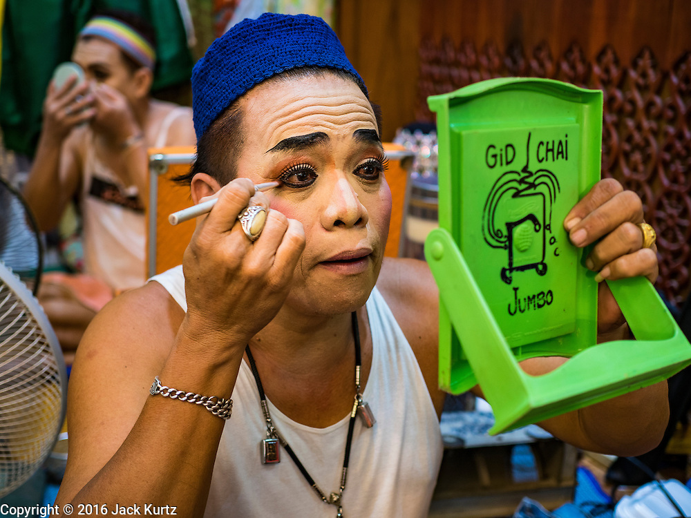"30 JANUARY 2016 - NONTHABURI, NONTHABURI, THAILAND: A performer puts on his eye makeup before a ""likay"" show at Wat Bua Khwan in Nonthaburi, north of Bangkok. Likay is a form of popular folk theatre that includes exposition, singing and dancing in Thailand. It uses a combination of extravagant costumes and minimally equipped stages. Intentionally vague storylines means performances rely on actors' skills of improvisation. Like better the known Chinese Opera, which it resembles, Likay is performed mostly at temple fairs and privately sponsored events, especially in rural areas. Likay operas are televised and there is a market for bootleg likay videos and live performance of likay is becoming more rare.     PHOTO BY JACK KURTZ"