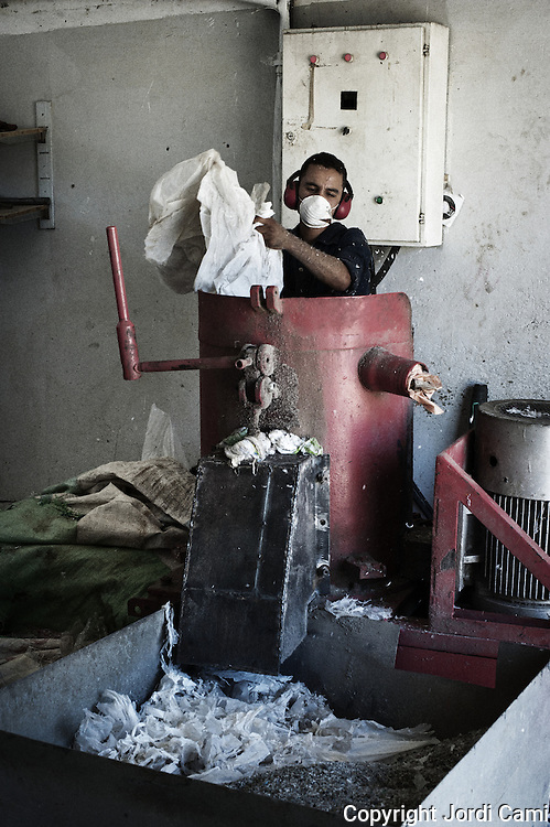 "Worker ""Zabbaleen"" in a machine that shreds plastic for reuse, recycling plant Katameya, who heads the NGO APE on the outskirts of Cairo. . In the middle of Manshiet Nasr a Cairo neighborhood is located Mokattam settlement known as ""Garbage City"" is inhabited by Zabbaleen, a community of about 45,000 Coptic Christians living for decades to recycle waste generated by the Egyptian capital: plastic, aluminum, paper and organic waste transformed into compost. Most part of the Association for the Protection of the Environment (APE), an NGO that works in the area, whose objectives are to protect the environment and improve the livelihoods of garbage scavengers in Cairo. According to the UN, the work is done in Mokattam is one of the ten best examples of world environmental improvement. El Cairo , Egipt, June 2011. ( Photo by  Jordi Camí )."