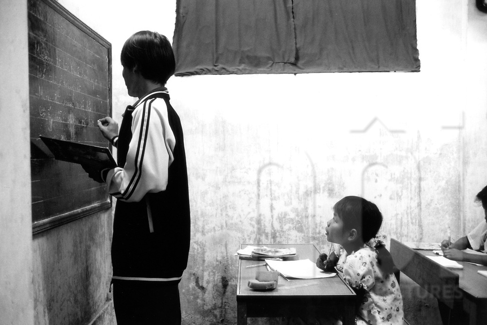 A teacher gives lessons to his young students in an old classroom in a Nha Trang school, Vietnam, Southeast Asia