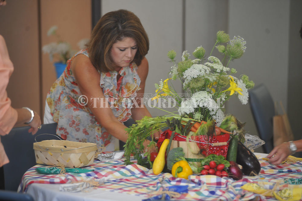 Christy Knapp decorates a table as the Oxford Garden Club hosts the Tombigbee Valley District Spring Workshop in Oxford, Miss. on Thursday, June 16, 2011. The theme for the various table decorations was farmers market.