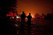 A young man leads his mother out of the floodwaters and to awaiting fire fighters. Brighton Beach NYC.<br />